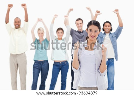 Close-up of a woman clenching her fists with people raising their arms in background - stock photo