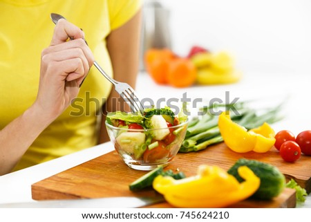 Close-up of a woman eating salad in the kitchen