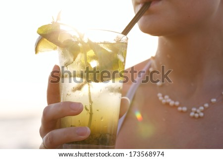 Close up of a woman enjoying a tropical mojito cocktail decorated with fresh fruit at the seaside at sunset sipping it through a straw on her summer vacation