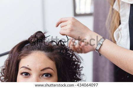 Close-up of a woman hairdresser making curls