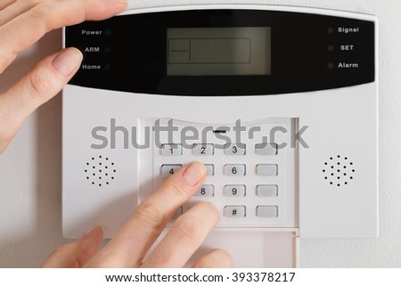 Close-up Of A Woman Hand Entering Code In Security System