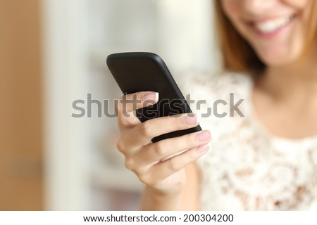 Close up of a woman hand using a smart phone at home with her smile in the background         - stock photo