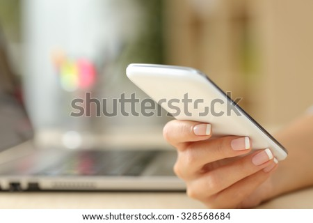 Close up of a woman hand using a white smart phone on a desk at home - stock photo