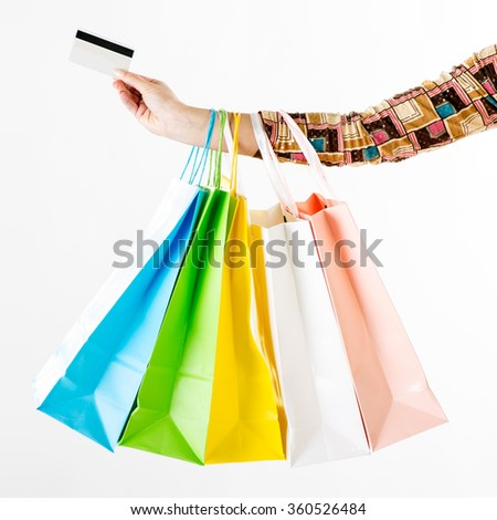 Close up of a woman hand with many shopping bags and credit card. White background. - stock photo