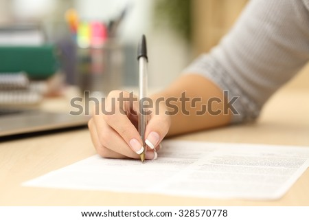 Close up of a woman hand writing or signing in a document on a desk at home or office - stock photo