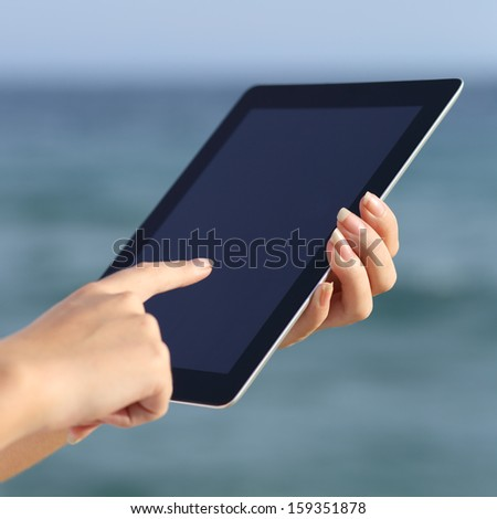 Close up of a woman hands holding and browsing a digital tablet on the beach with the sea in the background              - stock photo