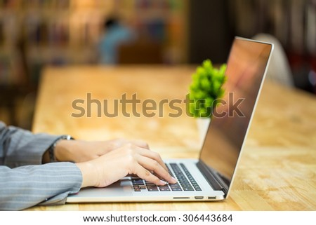 Close up of a woman hands working with a laptop in a coffee shop - stock photo