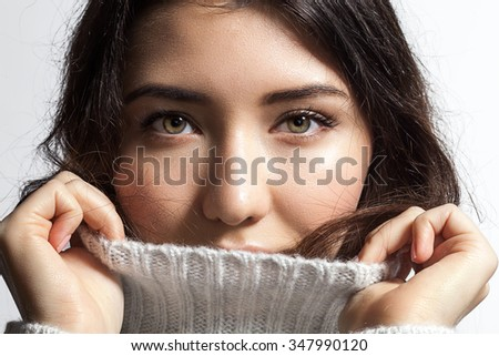 Close-up of a woman hides into the collar of fluffy white sweater - stock photo