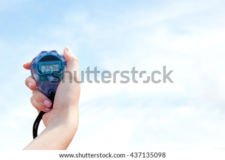 Close-up of a woman holding a chronometer to measure performance against blue sky with clouds - stock photo