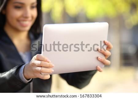Close up of a woman holding and watching a digital tablet in a park - stock photo