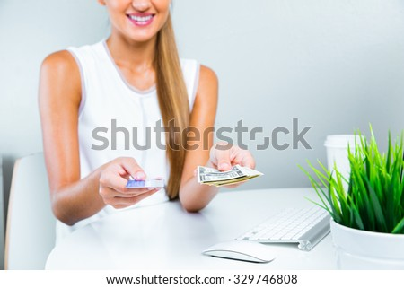 close up of a woman holding credit card and money , good credit history , credit score - stock photo