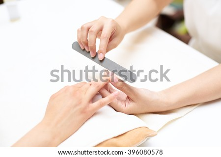 Close up of a woman in a nail salon receiving manicure - stock photo