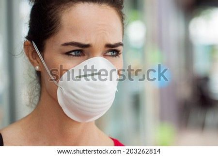 Close-up of a woman in the city wearing a face mask to protect herself from infection or air pollution. - stock photo