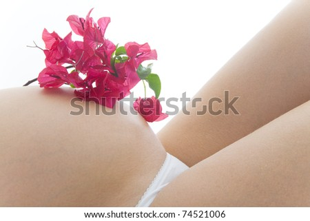 Close up of a woman in the sixth month of pregnancy with bougainvillea flowers on her bump and a white background - stock photo