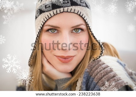 Close up of a woman in winter hat looking at the camera against snowflakes