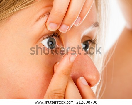 Close-up of a woman inserting comfortable soft contact lenses. - stock photo