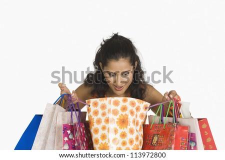 Close-up of a woman looking in shopping bags - stock photo