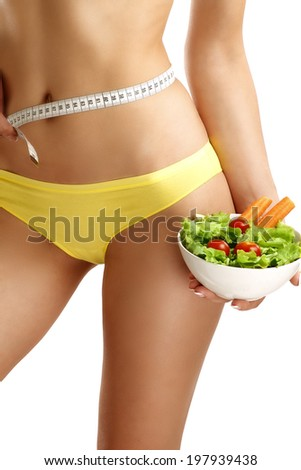 Close up of a woman measuring  hips with a salad in her hand on white