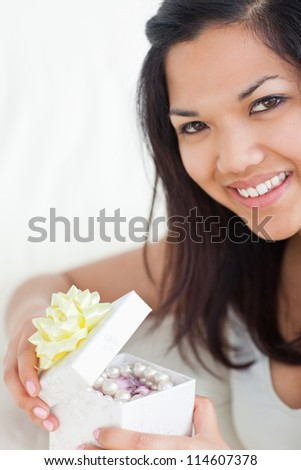 Close-up of a woman opening a gift box in a living room