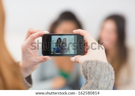 Close up of a woman photographing friends with smartphone at home - stock photo