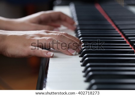 Close up of a woman playing piano. Focus is on her hand in shallow DOF.