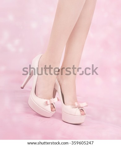 Close up of a woman's beautiful legs over pink background...