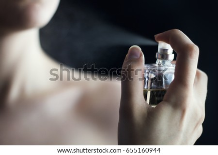 Close up of a woman's hand applying perfume with dark background