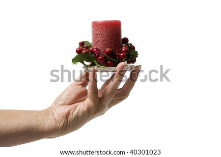 Close up of a woman's hand holding a Christmas candle isolated on a white background. - stock photo