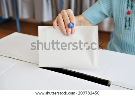 Close up of a woman's hand putting her vote in the ballot box - stock photo