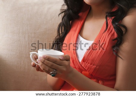 Close-up of a woman's hands holding a coffee cup - stock photo
