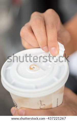 Close-up of a woman's hands holding a to go paper coffee cup while opening its plastic lid.