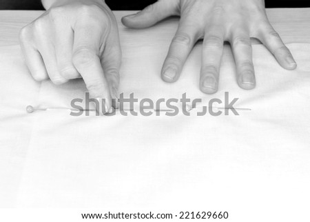 Close up of a woman's hands pinning large upholstery pins into plain fabric - monochrome processing - stock photo