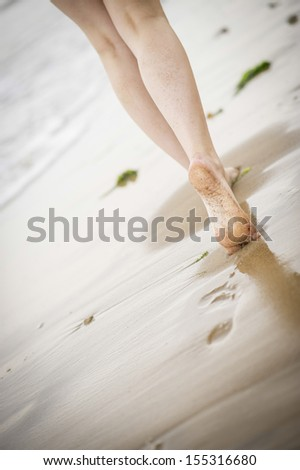 Close up of a woman's legs walking along the beach as the tide comes in