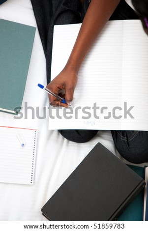 Close-up of a woman studying sitting on her bed at home - stock photo