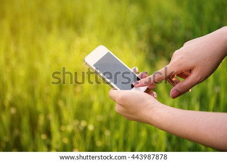 Close-up of a woman typing on mobile phone in green meadow