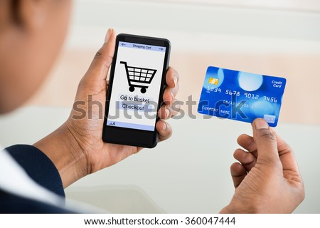 Close-up Of A Woman Using Card While Shopping On Mobile Phone - stock photo
