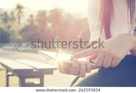 Close up of a woman using mobile smart phone outdoor, nature background. (vintage color tone) - stock photo