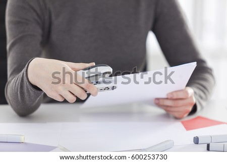 Close up of a woman wearing a gray sweater and holding a stapler in her hand. Concept of personal assistant work.