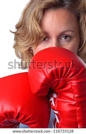 Close up of a woman who is wearing boxing gloves, white background. - stock photo