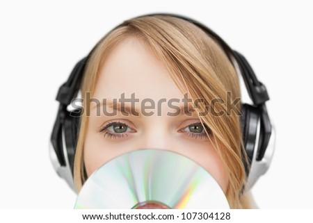 Close up of a woman with a cd in front of her face against a white background - stock photo