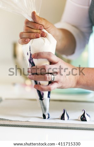 close up of a woman with decorating bag piping meringues - stock photo