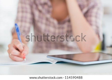Close up of a woman writing on a notebook in a living room - stock photo