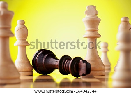 Close-up of a wooden chess table with the black king fallen down, surrounded by white pieces, symbol of lost power or political games - stock photo