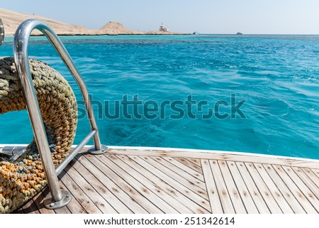 Close-up of a wooden deck end of a yacht and island on background - stock photo