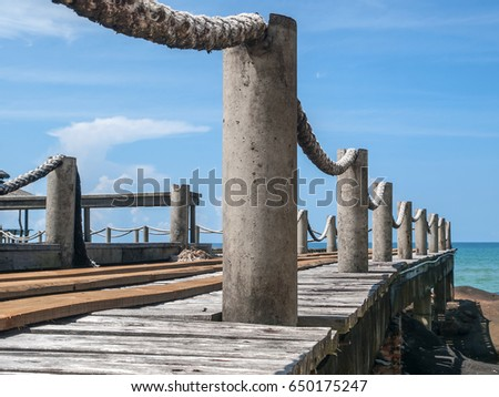 Close up of a wooden jetty at a resort on Ko Kut island in eastern Thailand. Ropes provide handholds along its length. Blue sky day.