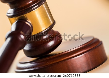 Close up of a wooden judge or auctioneers gavel with a brass band on a wooden base for delivering judgement - stock photo