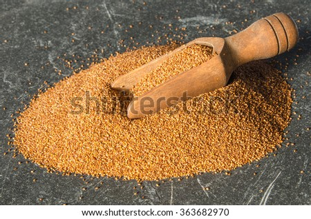 Close up of a wooden scoop in a mound of Teff, a gluten free ancient grain alternative, on a black slate surface   - stock photo