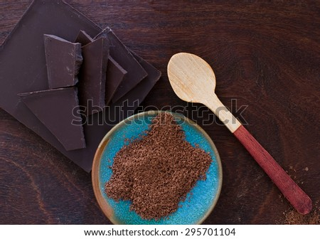 close up of  a wooden spoon, chocolate and cocoa powder on wooden background - studio shot  from above - stock photo