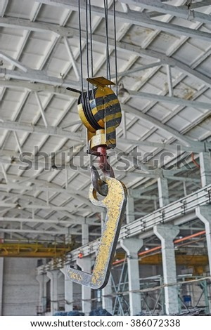 Close up of a yellow factory crane hook - stock photo