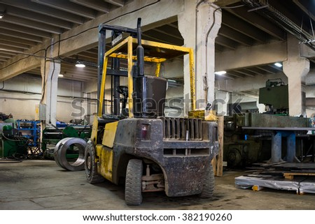close-up of a yellow forklift, with no driver, parked inside an industrial hall, with green industrial machinery and a roll of metal sheet in the background - stock photo